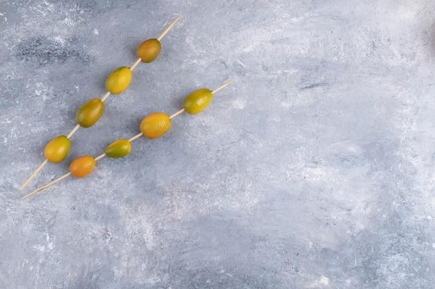 Eetstokjes met verse kumquats op een marmeren achtergrond. Gratis Foto