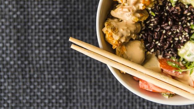 Eetstokjes op rijstkom met exemplaar-ruimte Gratis Foto