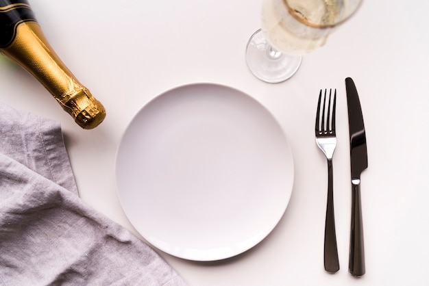 Eettafel met lege plaat en champagnefles op witte achtergrond Premium Foto