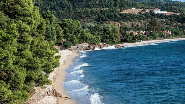 Egeïsche kust van griekenland, rotsachtige heuvels met groeiende bomen en struiken, strand met golven, gebouwen vlakbij de kust Gratis Foto