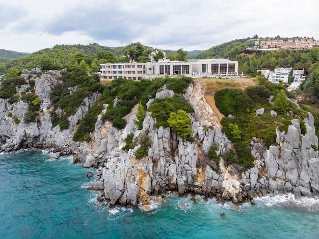 Egeïsche zeekust van griekenland, loutra-gebouwen gelegen nabij de rotswanden, groen en blauw water. uitzicht vanaf de drone Gratis Foto