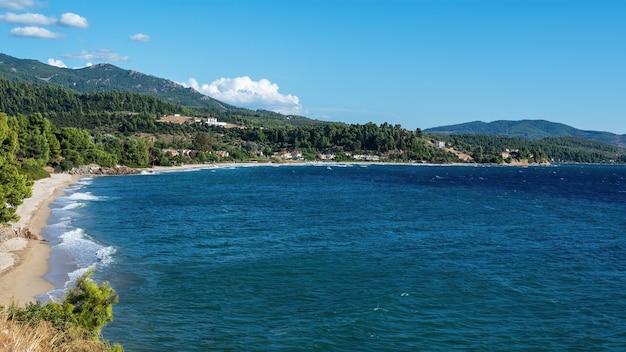 Egeïsche zeekust van griekenland, rotsachtige heuvels met groeiende bomen en struiken, gebouwen vlakbij de kust Gratis Foto