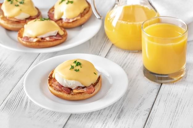Eggs benedict met spek op een witte plaat Premium Foto