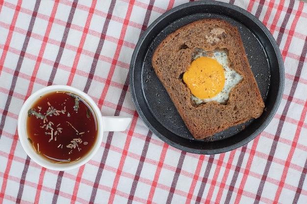 Ei toast brood en kopje thee op tafellaken. hoge kwaliteit foto Gratis Foto