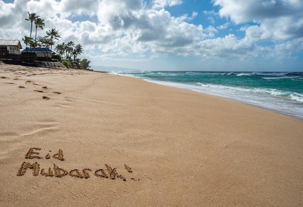 Eid mubarak geschreven in het zand op een strand in hawaï Premium Foto