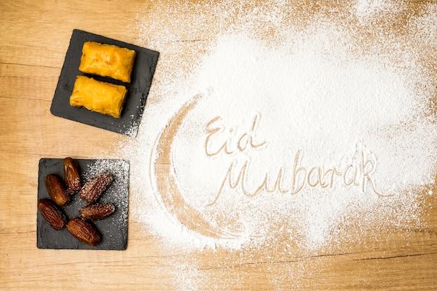 Eid mubarak-inscriptie op bloem met oostelijke snoepjes Gratis Foto