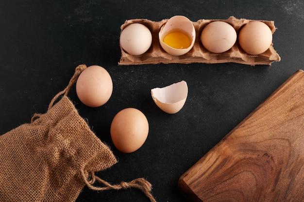 Eidooier in eierschaal op zwarte achtergrond in de kartonnen lade. Gratis Foto