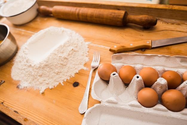 Eieren en bloem op houten tafelblad Gratis Foto