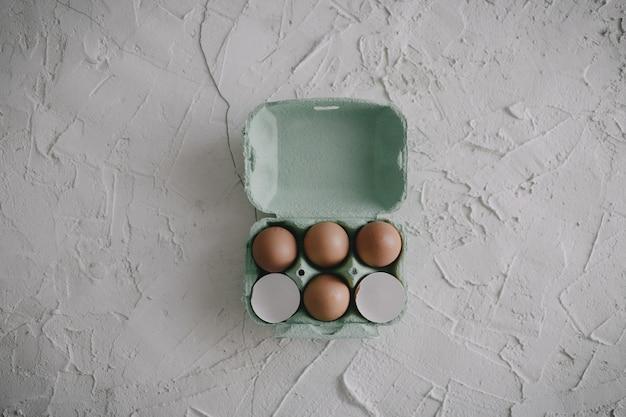 Eieren en eierschalen in een doos op tafel Gratis Foto