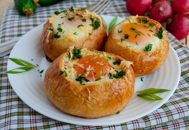 Eieren gebakken in een broodje met ham, kaas en kruiden. frans ontbijt. Premium Foto