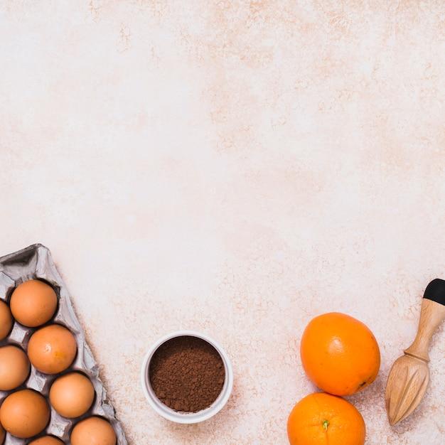 Eieren in karton; cacaopoeder; citrusvruchten en houten sappers op concrete achtergrond Gratis Foto