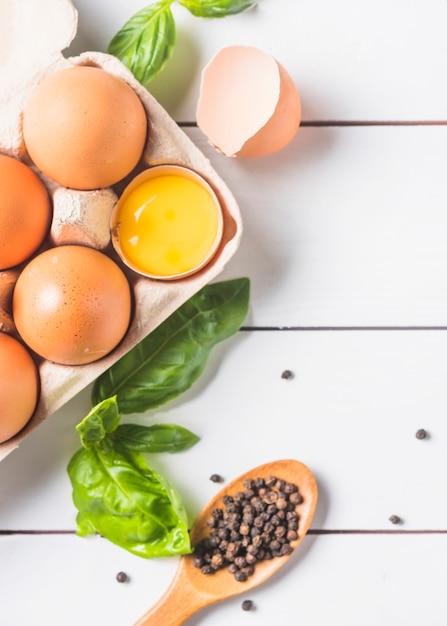 Eieren in karton met basilicumblad en peperbollen op houten plank Gratis Foto