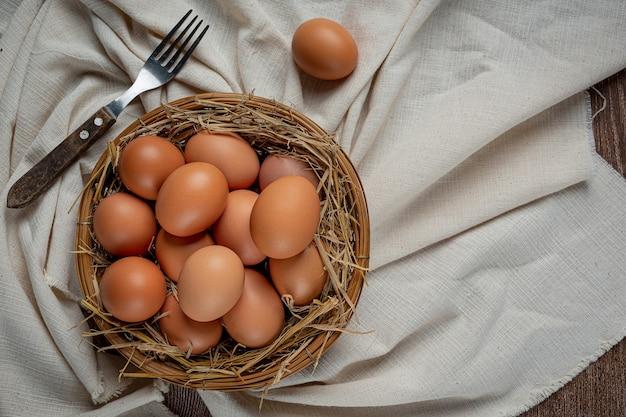 Eieren in kopjes op jute met droog gras. Gratis Foto