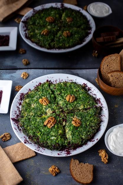 Eieren met groenten kuku vitamine rijk smakelijk met ontworpen walnoten op grijs bureau Gratis Foto