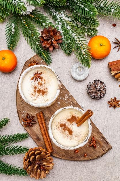 Eierpunch met kaneel en nootmuskaat voor kerst- en wintervakantie. zelfgemaakte drank in glazen met pittige rand. mandarijnen, kaarsen, cadeau. Premium Foto