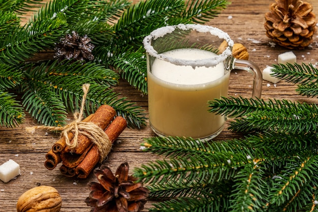 Eierpunchlikeur of cola de monococktail. klassieke winterdrank in glazen mok, xmas decoraties. groenblijvende takken, kaneel, walnoten, suiker. Premium Foto