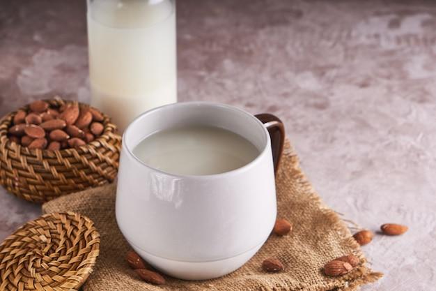 Eigengemaakte amandelmelk in een kop en een fles, amandelpitten op rustieke oppervlakte. alternatief eten en drinken. Premium Foto
