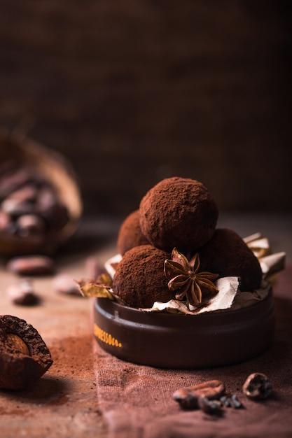 Eigengemaakte chocoladetruffels op de houten mening van de lijstclose-up. lekker vegetarisch snoep of balletjes met rauw cacaopoeder Premium Foto