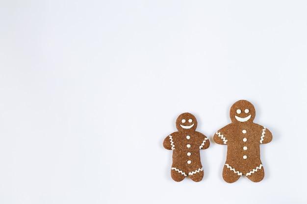 Eigengemaakte de peperkoekkoekjes van kerstmis die op witte achtergrond met exemplaarruimte worden geïsoleerd Premium Foto
