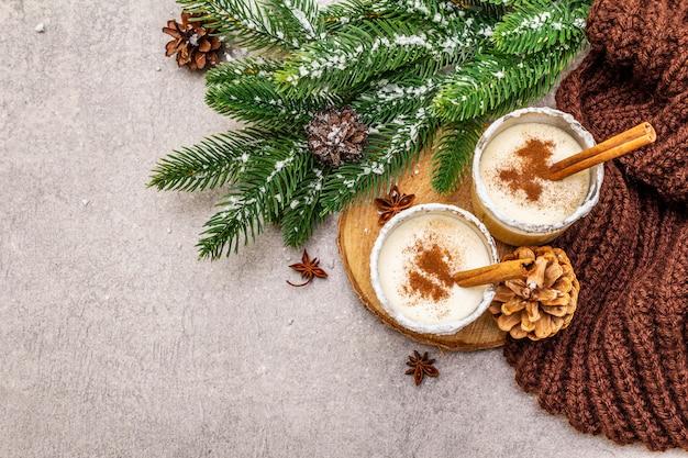 Eigengemaakte eierpunch met kaneel in glas. typisch kerstdessert. wintergroene sparbrunch, kegels, gezellige plaid, kunstmatige sneeuw. Premium Foto