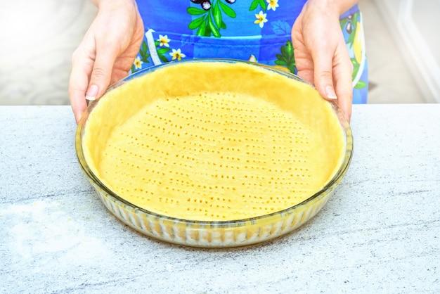 Eigengemaakte gebakjekorst. scherpe pastavoorbereiding, deeg op witte rustieke keukenlijst Premium Foto