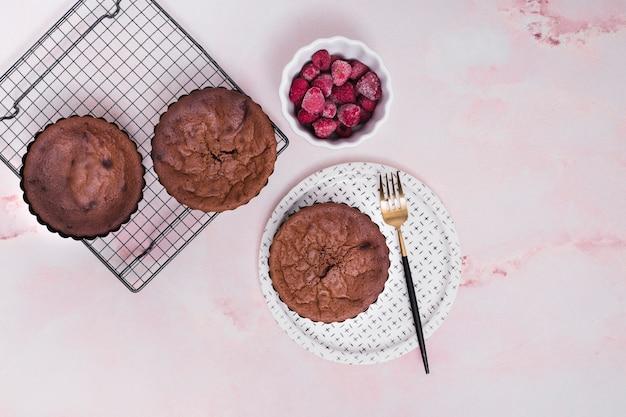 Eigengemaakte gebakken cakes op bakseldienblad en platen met bevroren frambozenkom tegen roze achtergrond Gratis Foto