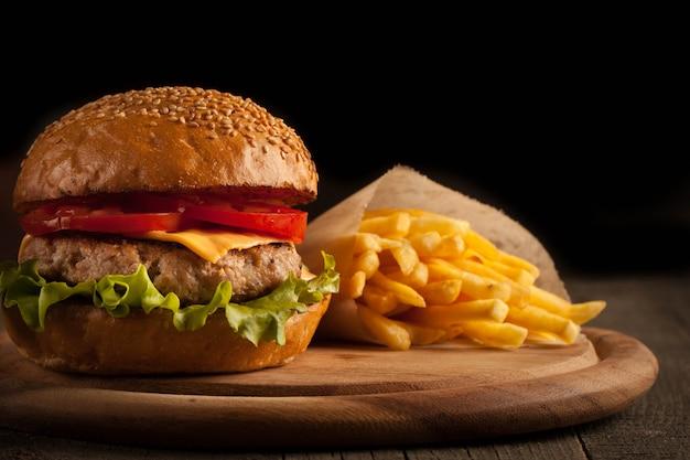Eigengemaakte hamburger met rundvlees, ui, tomaat, sla en kaas. cheeseburger. Premium Foto