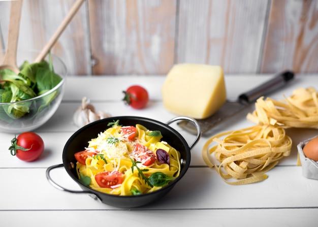 Eigengemaakte italiaanse spaghettideegwaren versieren met kazen; basilicumblaadjes en schijfje tomaat Gratis Foto