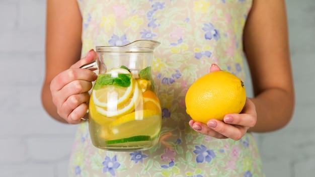 Eigengemaakte limonade en citroen die door een vrouw wordt gehouden Gratis Foto