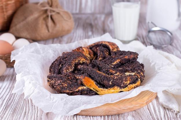 Eigengemaakte maanzaadtaart. gist ronde gesloten cake op een houten tafel met een linnen tafelkleed. kalach - rond brood. Premium Foto