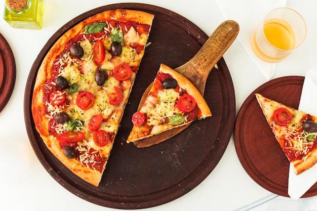 Eigengemaakte margheritipizza over houten cirkelraad Gratis Foto