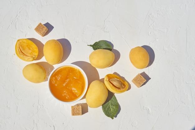 Eigengemaakte organische abrikozenjam en rijpe abrikozen en bruine suiker op witte achtergrond. Premium Foto
