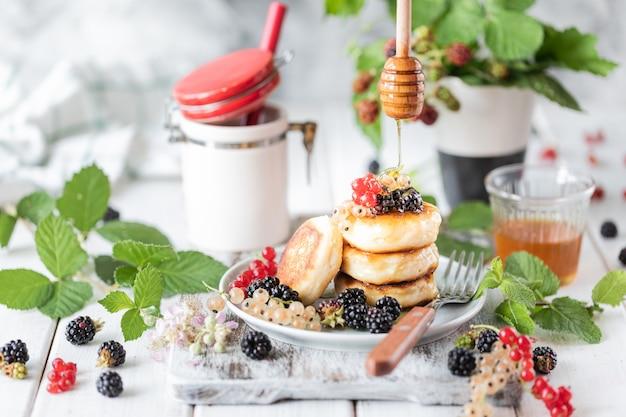 Eigengemaakte pannekoeken met bessen en wekker op witte houten Premium Foto