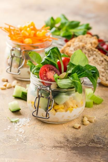 Eigengemaakte salade in glaskruik met maïssalade en groenten. Premium Foto