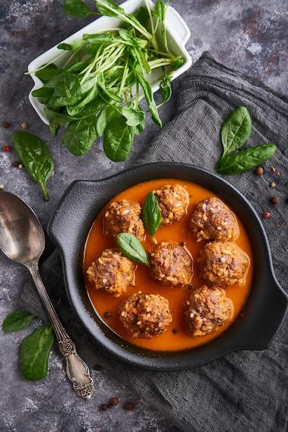 Eigengemaakte vleesballetjes met tomatensaus en spinazie in een plaat, hoogste mening Premium Foto