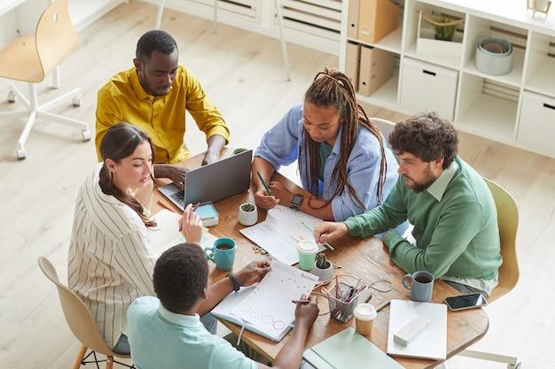 Eigentijds creatief team dat aan rommelige tafel samenwerkt met mokken en stationaire artikelen, teamwerk of studieconcept Premium Foto