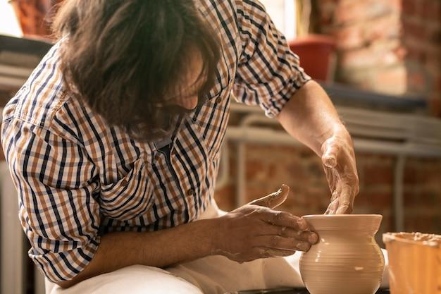 Eigentijdse jonge ambachtsman die door het draaien van aardewerkwiel zit tijdens het vormgeven van ruwe kleipot in zijn atelier Premium Foto