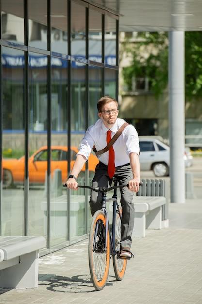 Eigentijdse jonge zakenman fietsten op zonnige zomerdag en langs de buitenkant van het zakencentrum op weg naar zijn werk Premium Foto