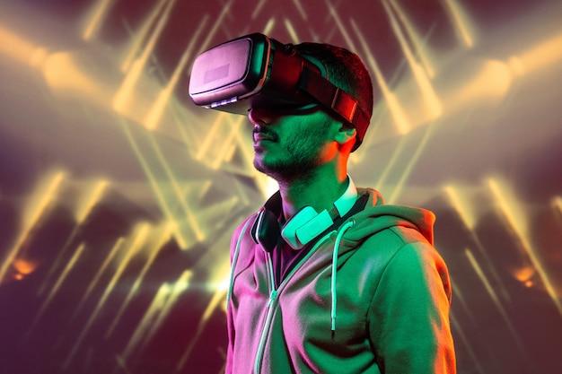 Eigentijdse man in vrijetijdskleding die in de virtuele wereld reist terwijl hij geïsoleerd staat tegen neonlichten Premium Foto