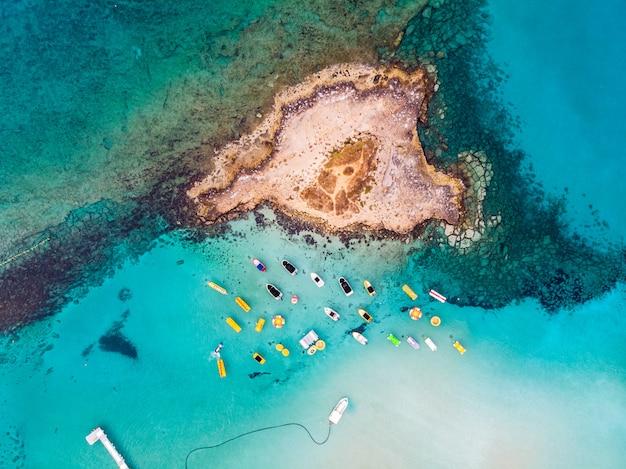 Eiland met boten geparkeerd in de buurt van vijgenboom baai strand Premium Foto