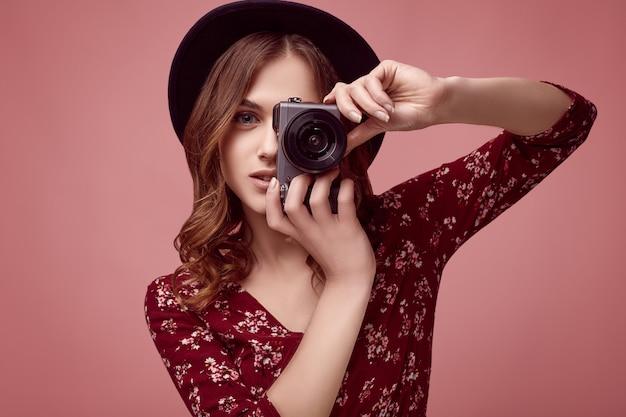 Elegant hipstermeisje in rode kleding, zwarte hoed en glazen met camera Premium Foto