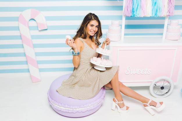 Elegant meisje dat in snoepwinkel werkt die smakelijke koekjes houdt en met gelukkige gezichtsuitdrukking glimlacht. dromerige jonge vrouw in vintage jurk zittend met heerlijk dessert in de buurt van toonbank met gebak. Gratis Foto