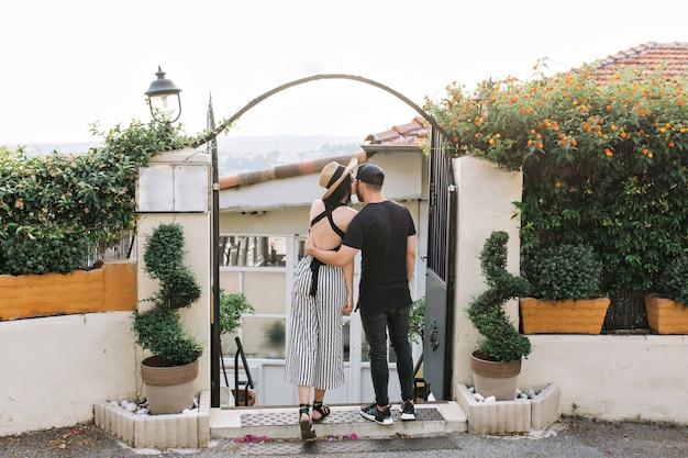 Elegant meisje in hoed kust haar vriend die in de ochtend voor zwarte poorten met exotische planten staat Gratis Foto