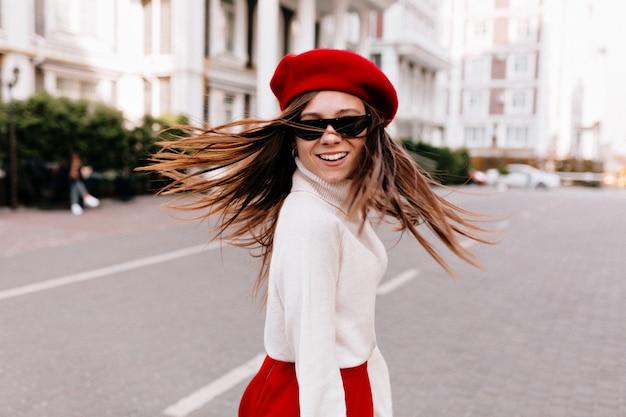 Elegant meisje met lang haar lachen tijdens het verkennen van het moderne deel van de stad. Gratis Foto