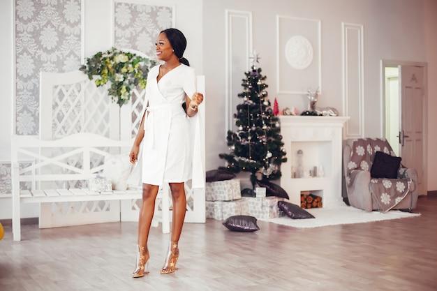 Elegant zwart meisje in de kerst ingerichte kamer Gratis Foto
