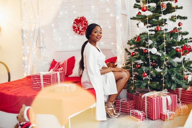 Elegant zwart meisje in een kamer met kerstmis Gratis Foto