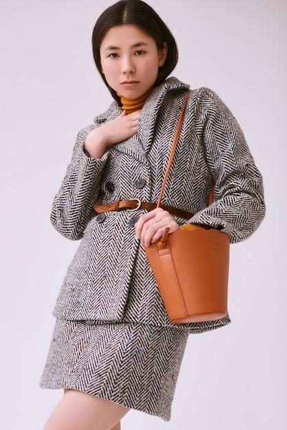 Elegante aziatische vrouw in modieuze wollen jas en klassieke rok Premium Foto