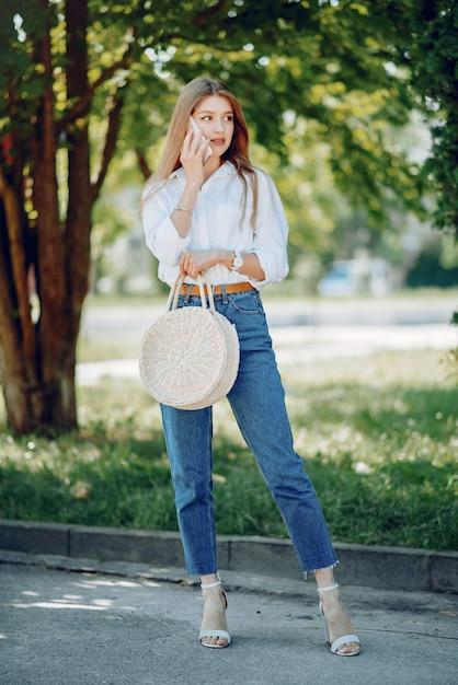 Elegante blonde in een zomer park met telefoon Gratis Foto