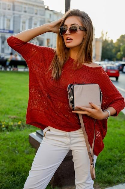 Elegante blonde vrouw in trendy herfst ourfit poseren op straat. een zonnebril, trui en witte jeans dragen. Gratis Foto