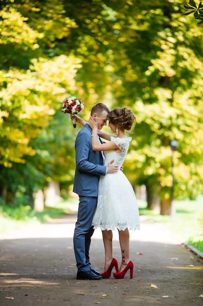 Elegante bruid en bruidegom poseren samen buitenshuis op een trouwdag Premium Foto